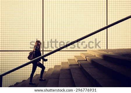young girl walking up stairs in city environment, square tiles on background. Space for copy text. Vintage filter applied. #296776931