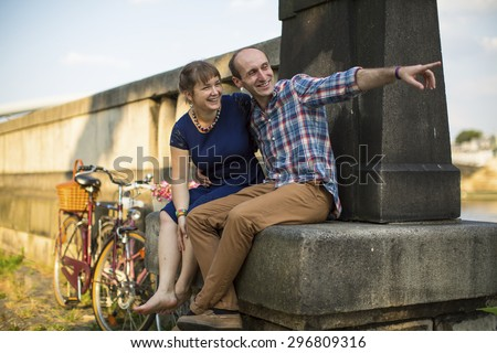 Happy young couple. Couple in love emotionally talking sitting on the urban stone waterfront. #296809316