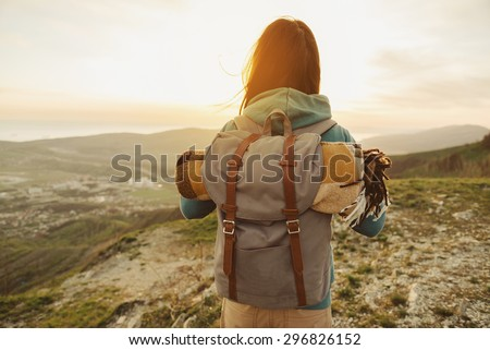 Hiker woman with backpack and sleeping bag walking in the mountains in summer at sunset Royalty-Free Stock Photo #296826152