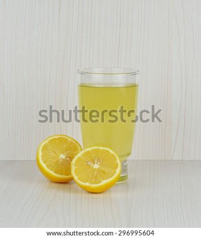 Lemonade with fresh lemon on wooden background. #296995604
