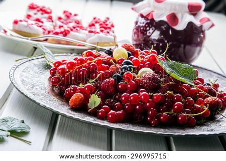 Plate with Assorted summer berries, raspberries, strawberries, cherries, currants, gooseberries. #296995715