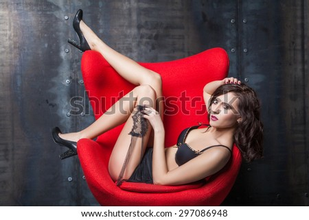 young attractive woman wearing sexy black lingerie reclining provocatively on chair. industrial interior. looking at camera. studio shot. Developed from RAW. retouched with special care and attention. #297086948