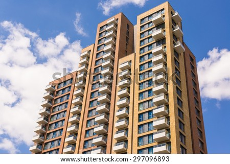 New block of modern apartments with balconies and blue sky in the background Royalty-Free Stock Photo #297096893