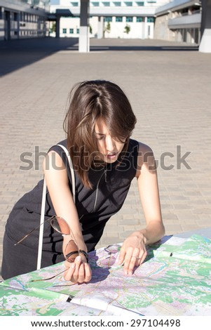 Attractive foreign female model looking on printed paper map in search of fastest directions to nearest hotel, restaurant, shopping center, main city square #297104498