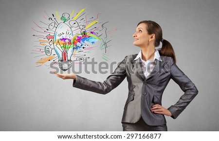 Smiling young businesswoman holding light bulb in palm #297166877