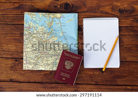 map, passport, notebook and cup of coffee on wooden table