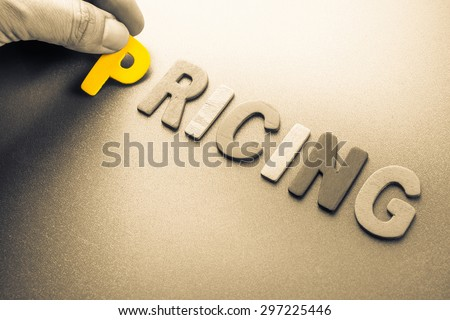 Hand arrange wood letters as Pricing word Royalty-Free Stock Photo #297225446