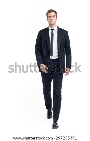Photo of young businessman wearing suit and walking seriously toward the camera. Isolated on white background #297235391