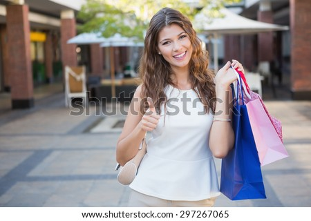 Portrait of smiling woman with shopping bags looking at camera and showing thumbs up at the shopping mall #297267065