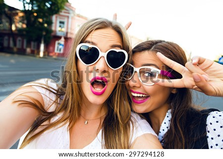 Cute outdoor portrait of funny pretty best friends girls having fun making selfie at city center, positive crazy emotions, traveling together in Europe, joy, vintage glasses, bright make up.