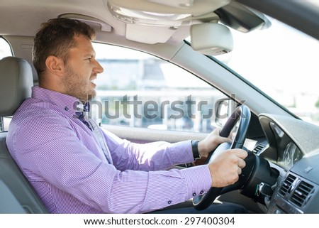 Young well-dressed man is driving his car with passion. He is looking forward with aggression #297400304