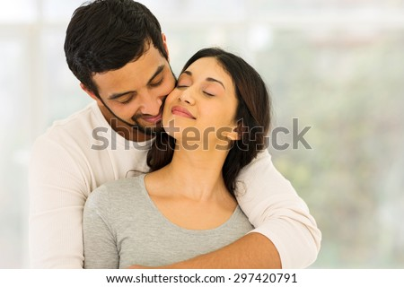 loving young indian couple embracing at home  #297420791