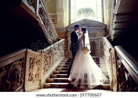 Wedding couple indoors is hugging each other. Beautiful model girl in white dress. Man in suit. Beauty bride with groom. Female and male portrait. Woman with lace veil. Cute lady and handsome guy Royalty-Free Stock Photo #297700607