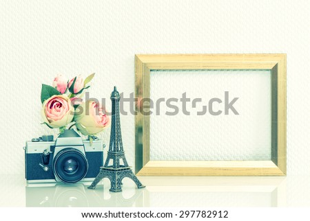 Golden picture frame, rose flowers and no name vintage camera. Retro style decoration with Eiffel Tower from Paris souvenir. Cross processing toned