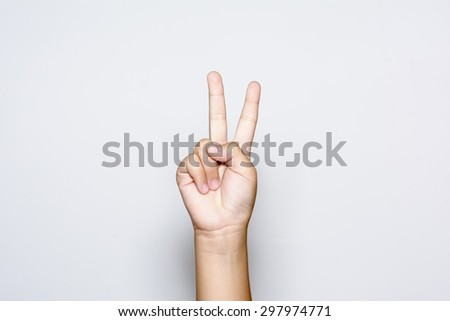 Boy raising two fingers up on hand it is shows peace strength fight or victory symbol and letter V in sign language on white background.  #297974771