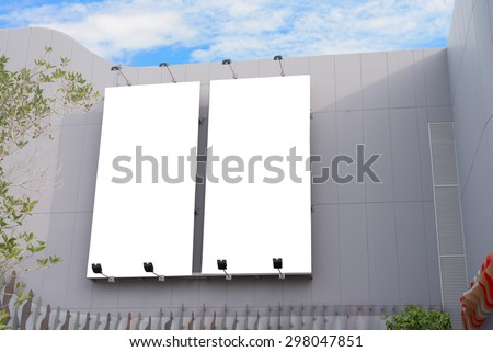 Blank poster board wall in modern shopping mall on a cloudy day.