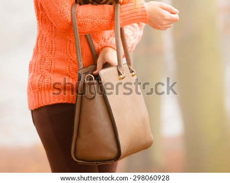 Autumn fashion. Woman fashionable girl wearing vivid clothing holding brown leather bag handbag in hand, walking in autumnal foggy park, outdoors #298060928