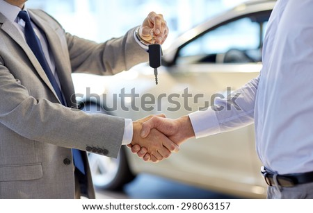 auto business, car sale, deal, gesture and people concept - close up of dealer giving key to new owner and shaking hands in auto show or salon #298063157