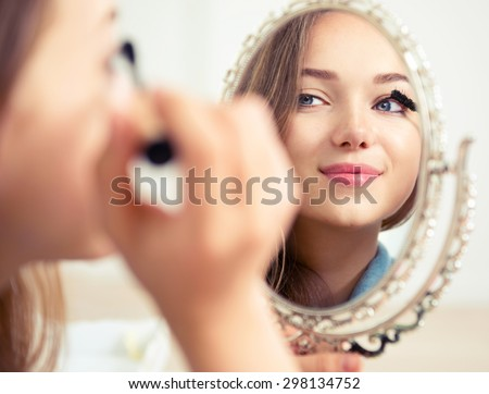 Beauty model teenage girl looking in the mirror and applying mascara make up. Beautiful young woman apply makeup #298134752