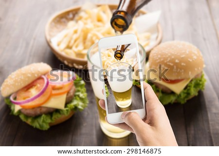 Using smartphones to take photos beer being poured into glass with gourmet hamburgers