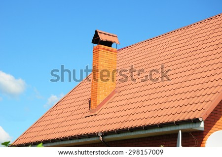 Faded red metal roof tile, rain gutter and chimney against blue sky. Bad roofing. #298157009