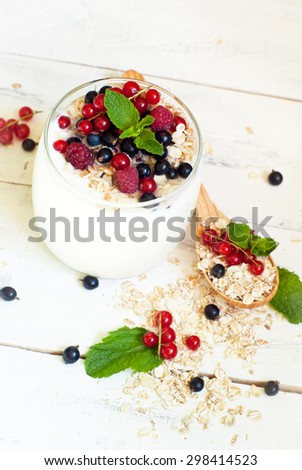 Homemade yogurt with berries and oat flakes in a glass jar #298414523