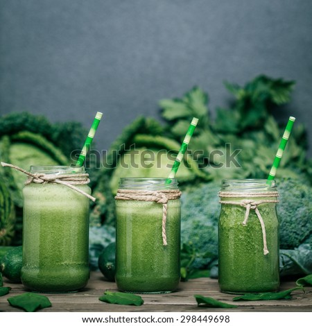 Blended green smoothie with ingredients on wooden table #298449698