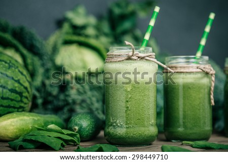 Blended green smoothie with ingredients on wooden table #298449710