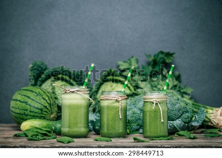 Blended green smoothie with ingredients on wooden table #298449713