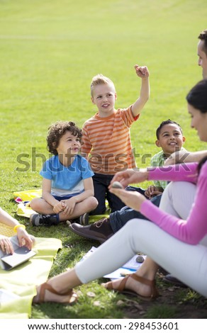 Small group of children sitting on the grass having a lesson outdoors. Only side of the teacher can be seen. The children look to be listening and enjoying themselves.  #298453601