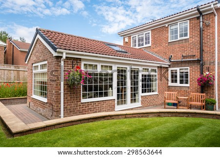 Modern Sunroom external / Modern Sunroom or conservatory extending into the garden, surrounded by a block paved patio #298563644