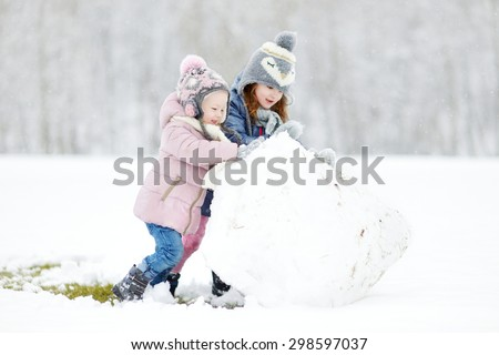 Two funny adorable little sisters making a snowman together in beautiful winter park during snowfall