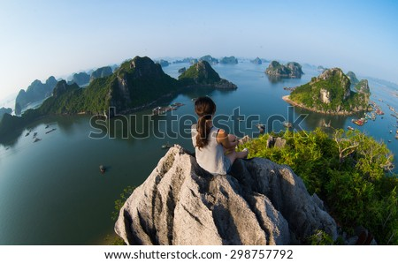 A young traveler girl sit on the top of mountain in Halong bay and enjoy the beauty of seascape. Young girl love wild life, travel, freedom. Royalty-Free Stock Photo #298757792