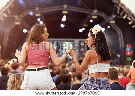 Two girls on shoulders in the crowd at a music festival Royalty-Free Stock Photo #298767065