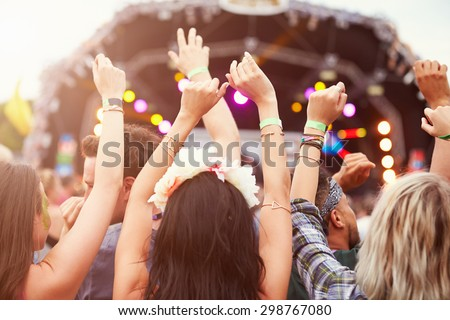 Audience with hands in the air at a music festival Royalty-Free Stock Photo #298767080