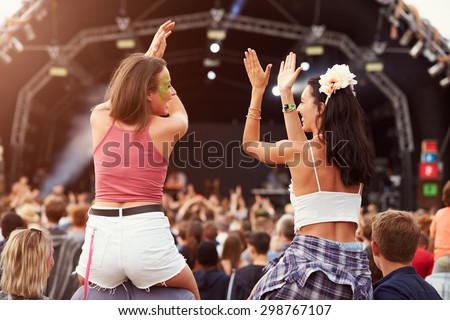 Two girls on shoulders in the crowd at a music festival #298767107