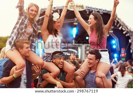 Friends having fun in the crowd at a music festival Royalty-Free Stock Photo #298767119