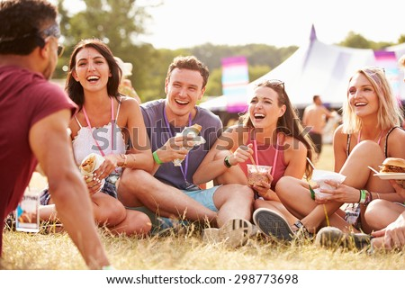 Friends sitting on grass and eating at music festival #298773698