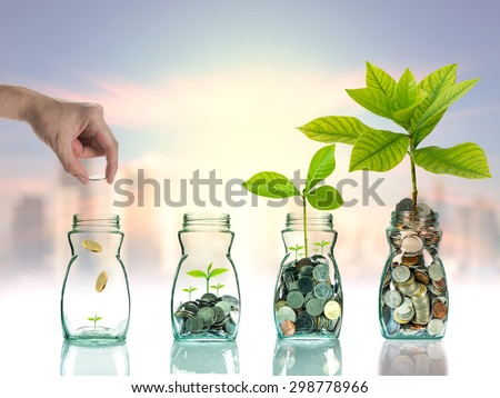 Hand putting mix coins and seed in clear bottle on cityscape photo blurred cityscape background,Business investment growth concept Royalty-Free Stock Photo #298778966