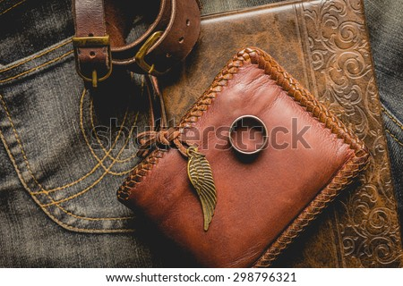 still life photography : Brown leather wallet, Leather wristbands, silver ring and adventure hat on jeans background,  men casual concept, vintage and retro style. Royalty-Free Stock Photo #298796321