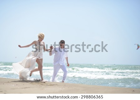 Beautiful laughing young wedding couple of man and woman in white running along ocean beach shore on windy weather sunny day outdoor on blue sky background, horizontal picture #298806365