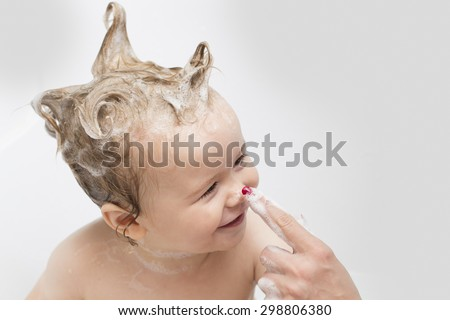 Little pretty wet baby boy in bath room with foam soap hair sitting and playing with mother's hand on white background, horizontal picture