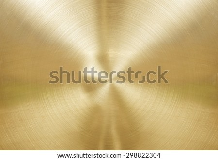 Gold brushed metal plate with reflections in circular.