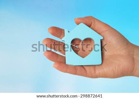 Female hand with model of house on color background #298872641