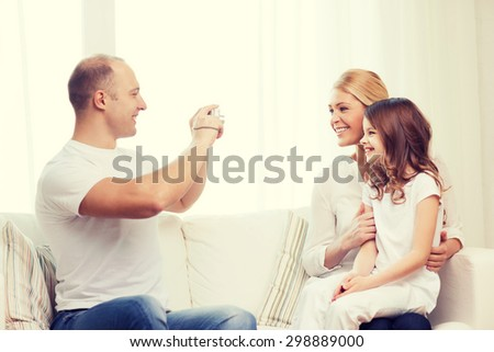 family, child, photography and home concept - smiling happy father taking picture of mother and daughter #298889000
