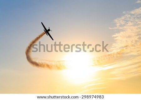 Silhouette of an airplane performing acrobatic flight at sundown. Trace of Smoke behind it #298974983
