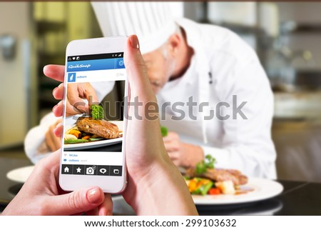 Hand holding smartphone against concentrated male chef garnishing food in kitchen