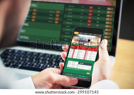 Businessman using smartphone against gambling app screen Royalty-Free Stock Photo #299107145