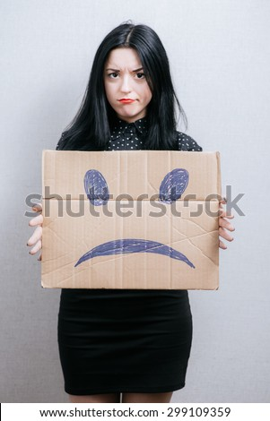 A woman holds a sad smiley on cardboard. On a gray background.