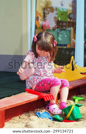 Child in the nursery fun in the sandbox pour out sand from the shoe. #299134721